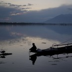 A Kashmiri fisherman prepares to bring to shore his Shikara, or traditional boat, after a days work at the Dal Lake on the outskirts of Srinagar, Indian controlled Kashmir. Nestled in the Himalayan mountains and known for its beautiful lakes and saucer-shaped valleys, the Indian portion of Kashmir, is also one of the most militarized places on earth.(AP Photo/Dar Yasin)<span class=