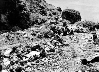 US Marines crouch behind rocks before the entrance to a cave where Japanese soldiers were holed up, during the invasion at Peleliu island in the Palau group on 10 October 1944.