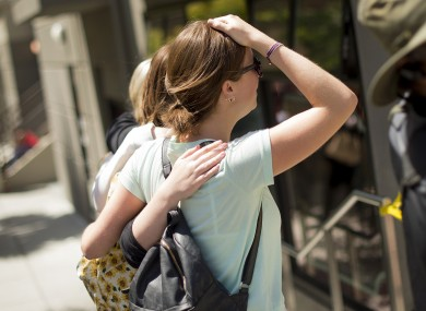 Women embrace after leaving flowers at the site of Monday night's balcony collapse in Berkeley.