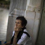 A woman sits at the main gate of the national bank of Greece as she waits her turn to withdraw a maximum of 120 euros ($134) for the week in Athens, in central Athens, Wednesday, July 15, 2015. Greece's Parliament votes Wednesday on an 85-billion-euro bailout deal meant to prevent the country's economy from collapsing.<span class=