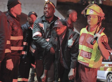 An injured passenger is helped to an ambulance at the Booysens train station near Johannesburg this evening