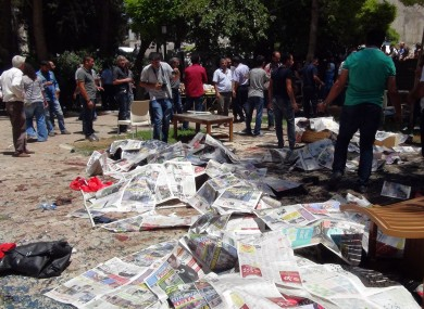 Dead bodies covered by newspapers at the site of the explosion.