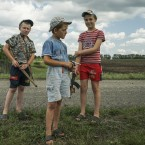 Local children holding toy guns stand at the site of the crashed Malaysia Airlines Flight 17 plane, near the village of Hrabove, eastern Ukraine, Thursday, July 16, 2015. A year since a Malaysia Airlines Boeing 777 was blown out of the sky over war-ravaged eastern Ukraine, killing 298 people, there has been little official word of progress in determining what brought down Flight MH17. <span class=