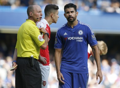 Referee Michael Dean holds a yellow cards after booking both Chelsea's Diego Costa, right, and Arsenal's Gabriel.