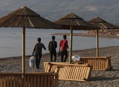 File photo: Three Pakistani Migrants walk on the beach of the island of Kos
