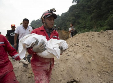 A fireman carrying the body of a child recovered from the landslide in Cambray
