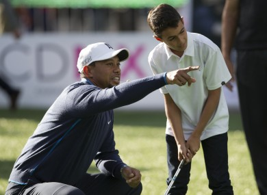 Tiger Woods gives advice to a young golfer earlier this week.