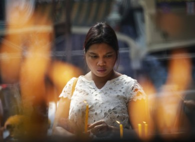 A Thai woman holding an incense stick during prayer at the festival