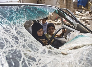 Yemeni girls play in a car damaged by Saudi-led airstrikes in the capital Sana'a