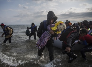 Migrants and refugees disembark from a dinghy after their arrival from Turkey on the Greek island of Lesbos on Saturday.