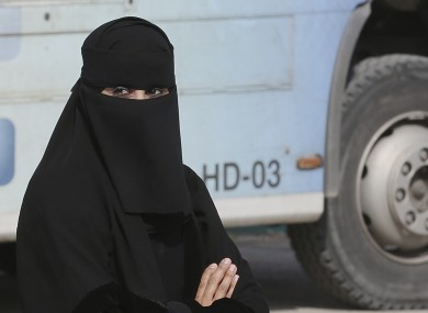 A Saudi woman waits outside a polling centre as she prepares to cast her ballot.