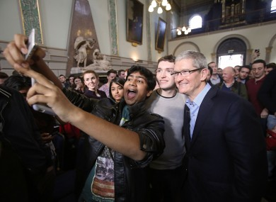 Apple CEO Tim Cook poses for selfies with students at Trinity College in November 2015.