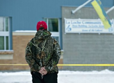 A man holds a rosary as police investigate the scene of a shooting.