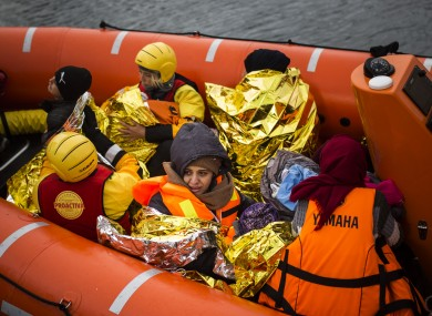 Refugees and migrants onboard a dinghy arriving to the Greek island of Lesbos yesterday