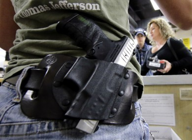 A woman wears her gun on her hip while working at the Spring Guns and Amo store in Texas.