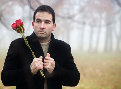 An Irish man hangs around a forest with some roses - no doubt awaiting his Valentine's Day present.