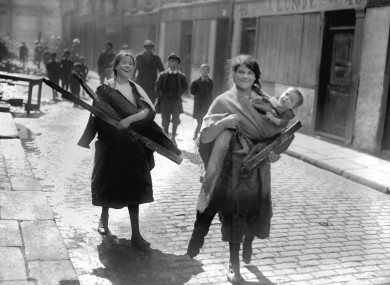 Children carry firewood from the rubble of Sackville Street, now O'Connell Street in the immediate aftermath of the Rising