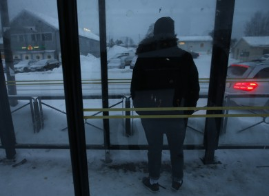 Elyas, 17, whose legal guardian in Norway asked that his surname not be published, waits at a bus stop in Alta, northern Norway.