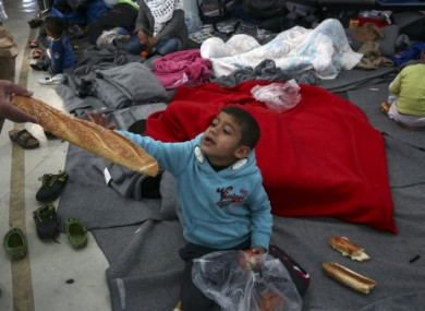 A boy is given a loaf of bread inside a passenger terminal which is used as a temporary shelter for refugees and migrants at the Athens' port of Piraeus