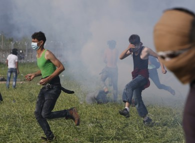 Migrant men coming under fire with tear gas at the Macedonian border
