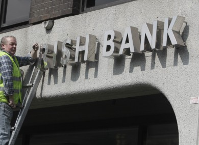 A workman removes the signage from Anglo Irish Bank headquarters at St Stephen's Green in Dublin