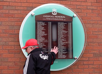A Liverpool fan touches the Hillsborough memorial outside Anfield.