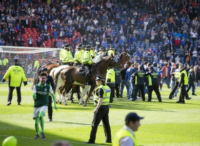 Police attempt to guide fans off the Hampden Park pitch.