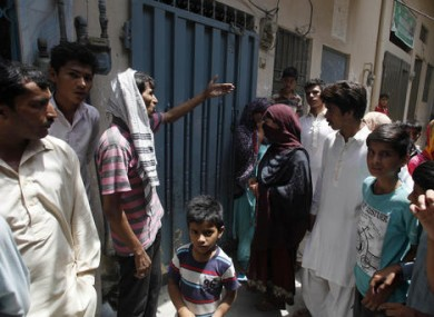 Local residents gather outside the home of Parveen Rafiq