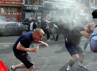 English fans run after getting sprayed with pepper spray by French police during scuffles in downtown Lille, northern France, earlier today.