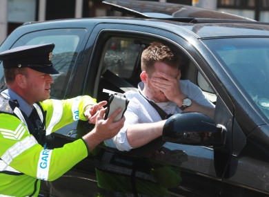 A garda performs a staged breathalyzer test with posed model driver.