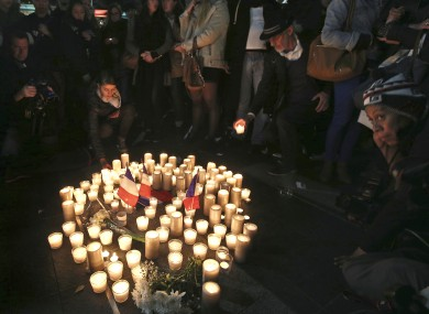 People place candles in a circle during a vigil in a tribute to the victims of the Bastille Day tragedy, in Sydney, Australia, Friday, July 15, 2016.