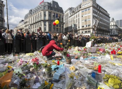 A woman lays flowers on a memorial to victims of the Brussels attacks.