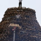 Men stand on a bonfire under construction in the Ballymacash area of Lisburn.<span class=