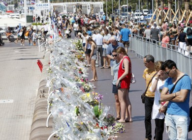 People look at flowers at the Promenade des Anglais in Nice.