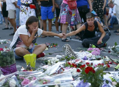 People pay tribute to the victims at the site of a deadly truck attack on the famed Promenade des Anglais in Nice, southern France.