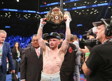 Carl Frampton holds up his championship belt after his WBA Super World Featherweight Championship fight against Leo Santa Cruz at the Barclays Center in the Brooklyn borough of New York on Saturday.