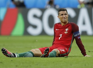 Portugal's Cristiano Ronaldo sits on the pitch after a challenge during the Euro 2016 final soccer match between Portugal and France at the Stade de France.