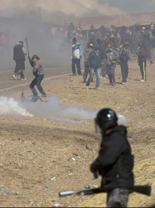 miners clash with the police as they run from clouds of tear gas during protests in Panduro, Bolivia.