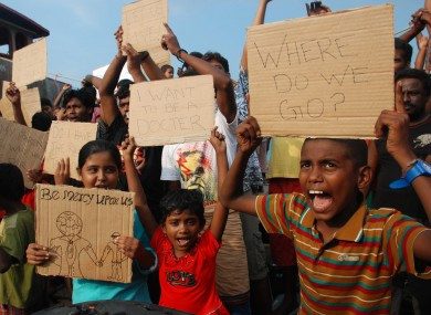 File image: Sri Lankan asylum seekers who were caught in Indonesian waters while trying to sail to Australia hold up posters during a demonstration.