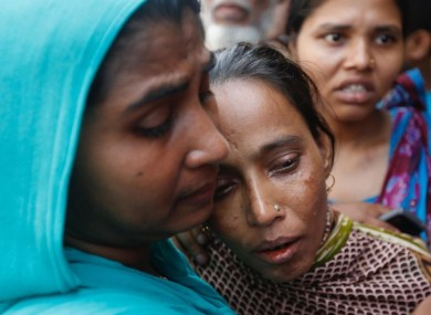 A Bangladeshi woman consoles another woman who lost a relative in the fire.