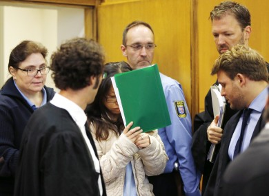 One of the accused covers her face entering a court in Frankfurt.