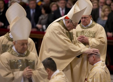 Cardinal George Pell poses his hands on the head of a newly ordained bishop.