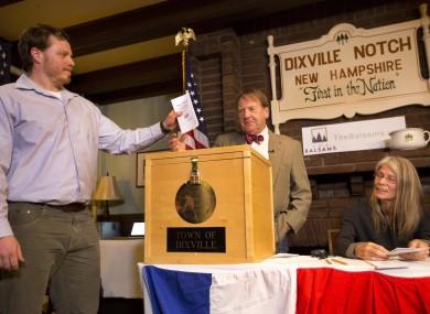 Dixville Notche's first voter Clay Smith drops his ballot into the box as moderator Tom Tillotson watches.