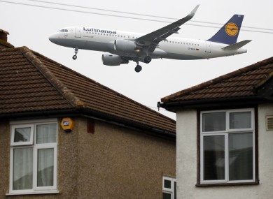 A Lufthansa plane on its final approach to landing passes over the rooftops of nearby houses at Heathrow Airport.
