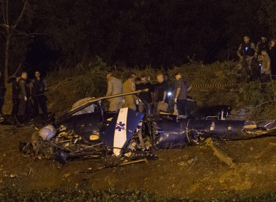Police gather at the scene of the crashed helicopter