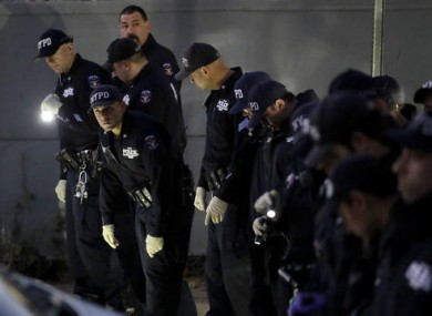 New York City Police officers search for clues on a street where a shooting took place in the Bronx borough of New York.