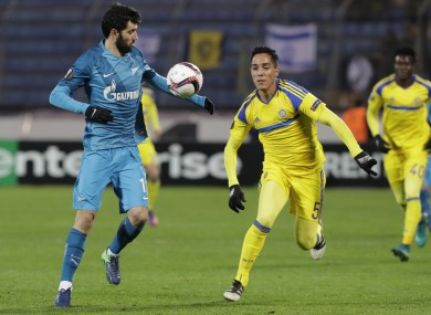 Luis Neto of Zenit St.Petersburg , left, struggles for a ball with Ezequiel Scarione of Maccabi Tel-Aviv.