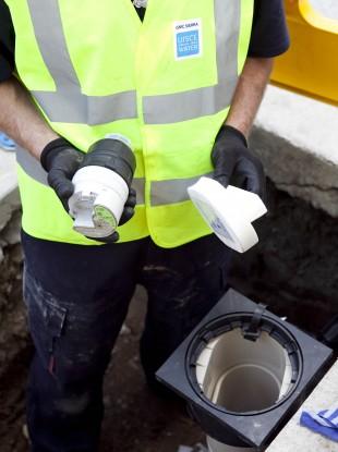 Worker installing a water meter.