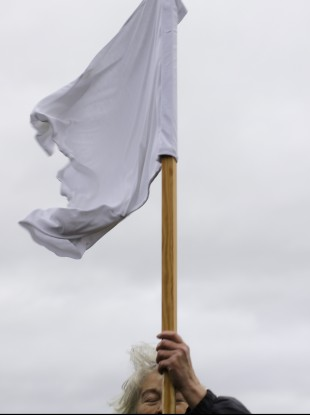 A demonstrator holds a white flag as she attends the Civil March for Aleppo at the airfield of the former airport Tempelhof in Berlin last Monday.
