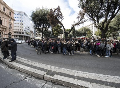 Students and teachers stand outside a highs chool after it was evacuated following three earthquakes which hit central Italy in the space of an hour
